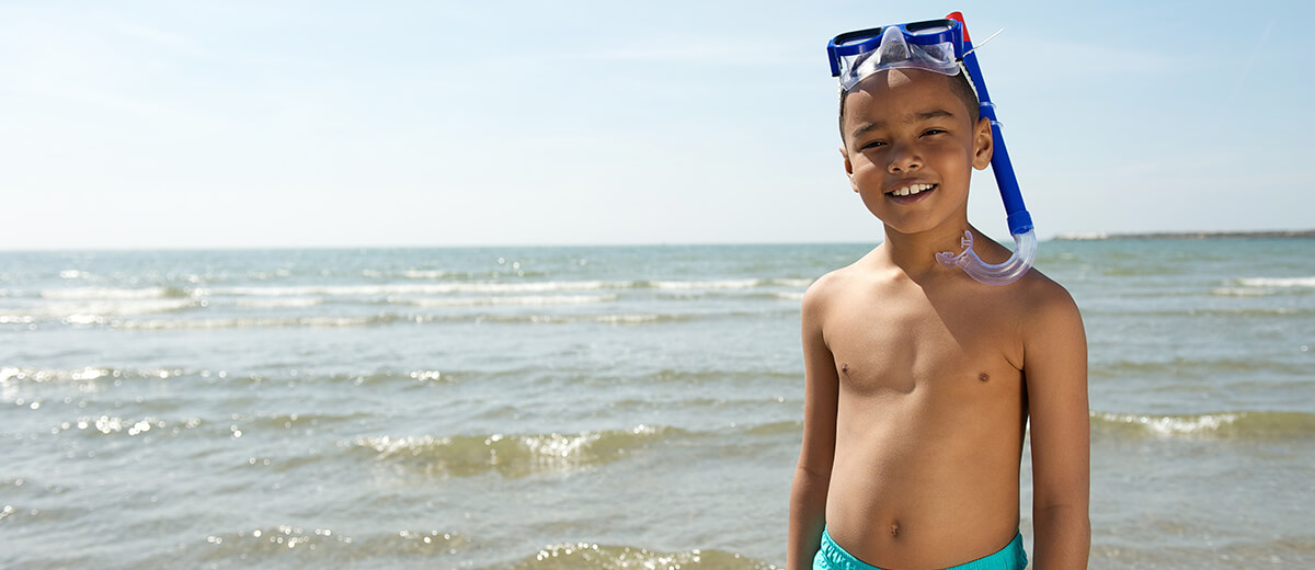 Child with goggles on beach